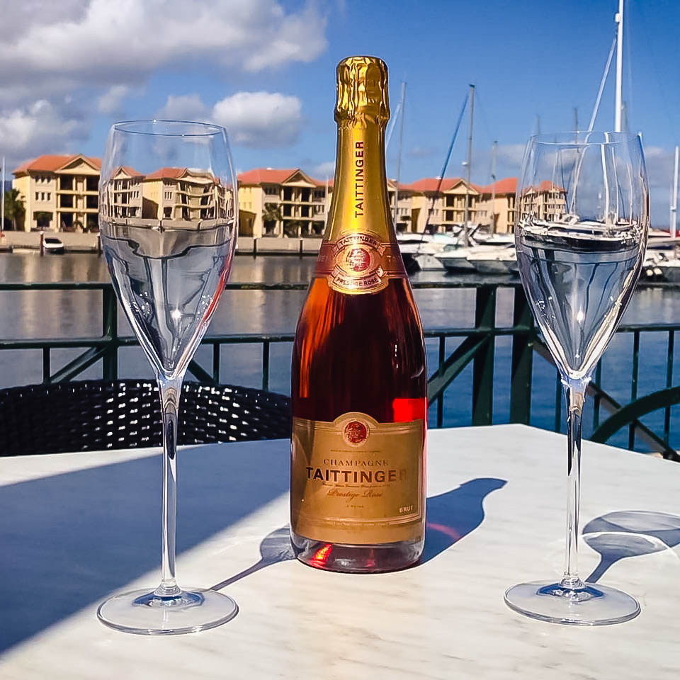 Champagne bottle with two glasses on a table in front of a marina