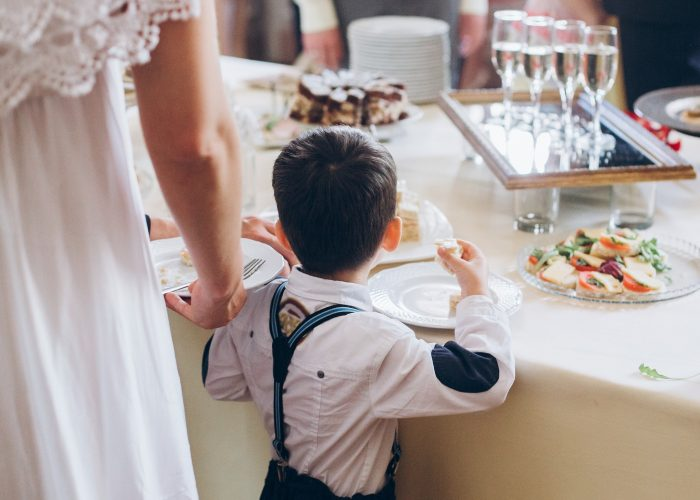 Little boy eating food appetizers on table at wedding reception